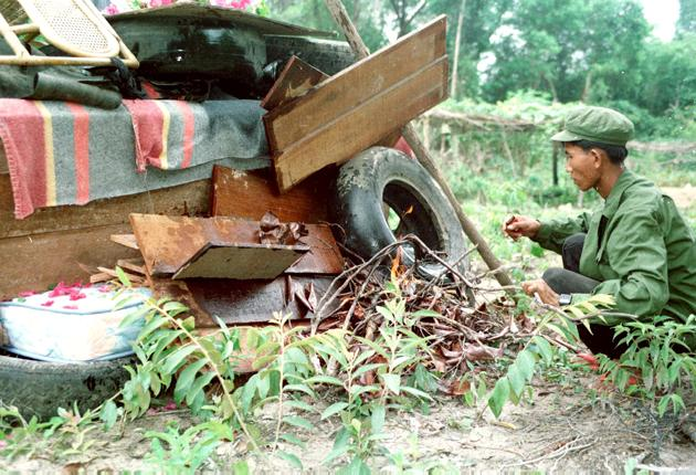 A Khmer Rouge fighter lights a hastily built pyre of mattresses, car tyres and old chairs beneath the coffin of his former leader, Pol Pot, in 1998