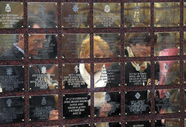Relatives are reflected in the Basra Memorial Wall of rededication at the National Memorial Arboretum in Alrewas, central England