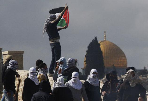 A Palestinian demonstrator holds a flag during clashes in east Jerusalem