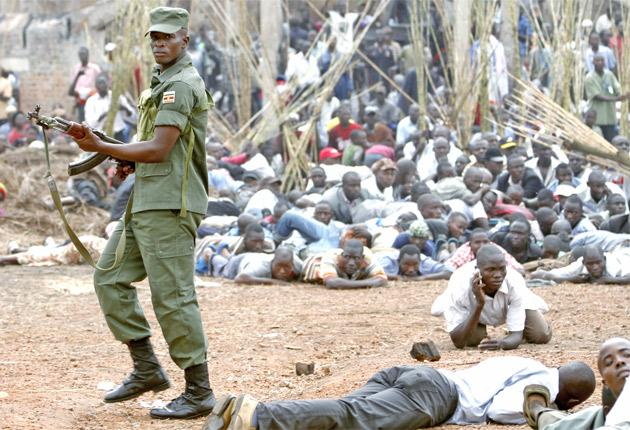 Ugandan soldier shoots into the air to disperse crowds at the fire-ravaged Kasubi royal tombs near Kampala yesterday
