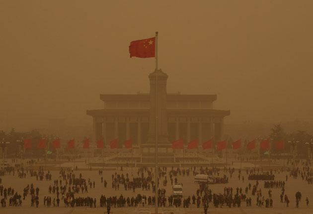 The sand covered Beijing, causing workers and tourists to muffle their faces in vast Tiananmen Square