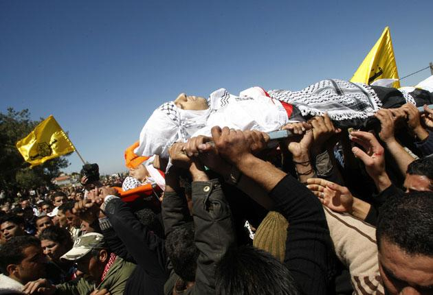 Palestinian mourners carry the bodies of teenagers Mohammed Qadus and Osaid Qadus to their graves