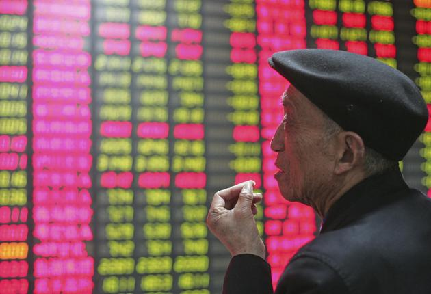 Risky business: An investor looks at the stock-price monitor at a private securities company in Shanghai last week