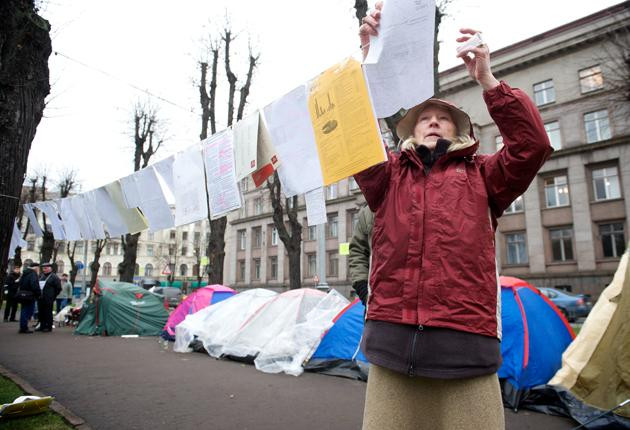 A Latvian woman places documents, detailing government  mistakes, by a tent city in front of the office of the country's Prime  Minister Valdis Dombrovskis