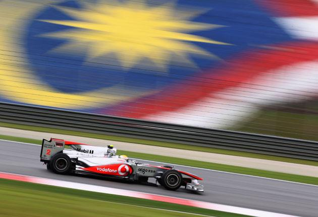 Lewis Hamilton flies past the Malaysian flag at the Sepang circuit