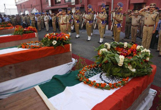 Police and soldiers perform a guard of honour yesterday for their colleagues killed in a Maoist attack in Chhattisgarh