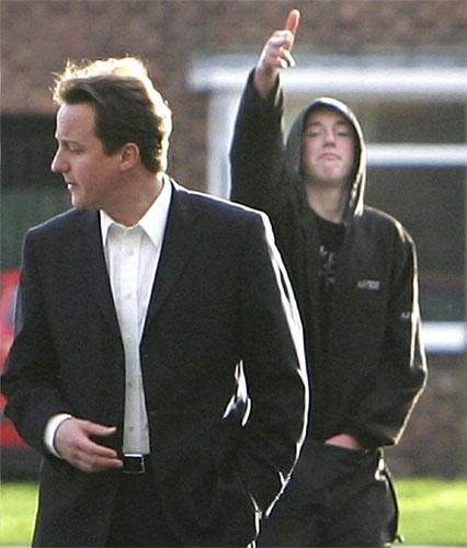 Ryan was snapped in 2007 making the 'click-bang' gesture behind an oblivious David Cameron who had been visiting a community project in Benchill