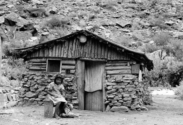 Two children of the Havasupai sit outside a house made of crude stones and logs, at Supai village in Havasu Canyon, in 1942