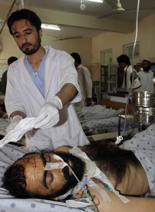 A medic helps a casualty of a Kandahar City blast yesterday