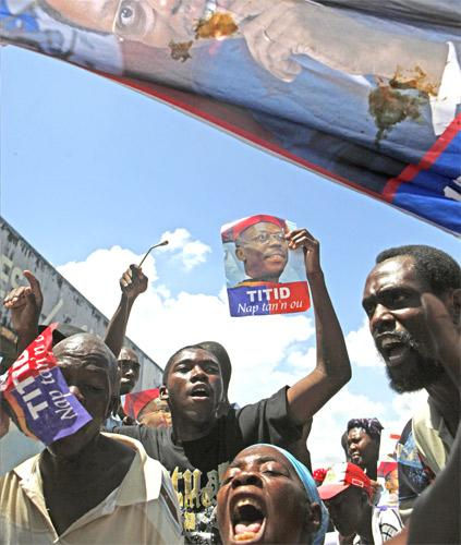 Protesters hold images of Haiti's former president, Jean-Bertrand Aristide, in Port-au-Prince, demanding that the incumbent, René Préval, step down