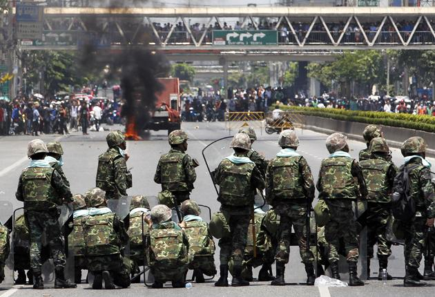 A tyre burns as Thai soldiers clash with anti-government protesters at Bangkok's financial district May 14, 2010. The Thai army fired rubber bullets into Lumphini Park in central Bangkok on Friday after gunshots were heard near an encampment that anti-gov