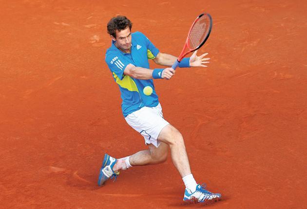 Andy Murray hits a backhand to Juan Ignacio Chela during his rain-hit match at Roland Garros yesterday