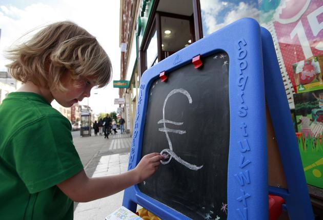 Noah Hall, five, draws a pound sign outside an early learning centre in Kensington, London, on Friday. Experts say that even without child trust funds, there will be many savings options left for children