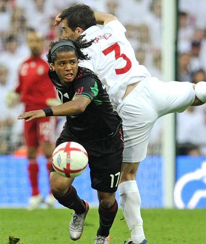 Giovani dos Santos takes the ball past England's Leighton Baines at Wembley last week