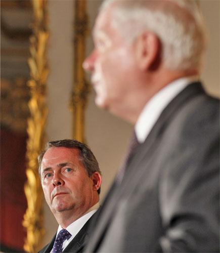 Liam Fox, left, looks to Robert Gates during a news conference at Lancaster House in London yesterday
