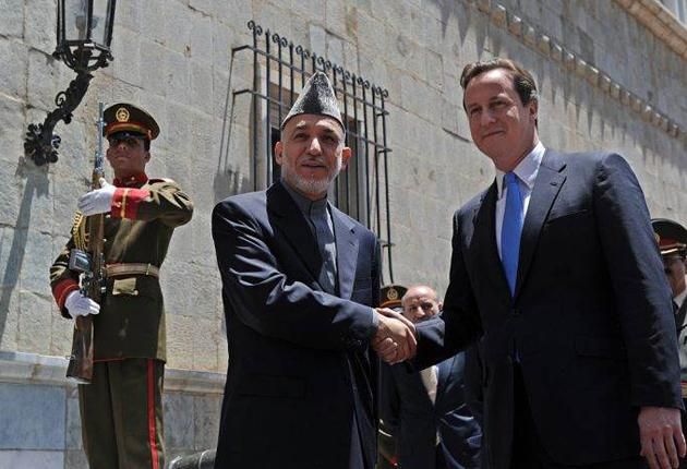 David Cameron shakes hands with President Hamid Karzai yesterday on his first visit to Afghanistan as Prime Minister