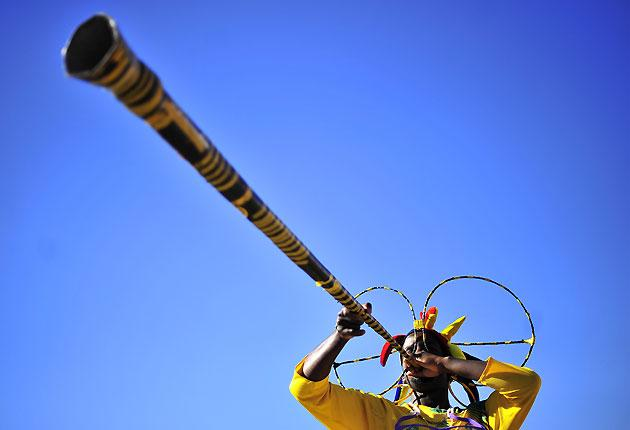 A football fan blows an extra-long vuvuzela horn on the first day of the 2010 World Cup in Cape Town