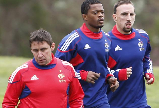 Patrice Evra (centre) and Franck Ribery run past fitness coach Robert Duverne during a France training session yesterday