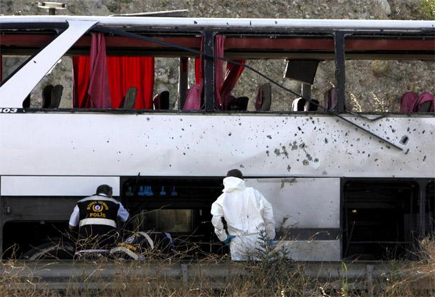 Forensic officers search the military bus after the blast