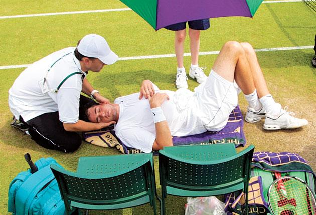 John Isner receives treatment during his second-round defeat yesterday