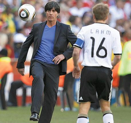 Joachim Löw, the Germany coach, knocks the ball back to his captain Philipp Lahm during his side's victory over England