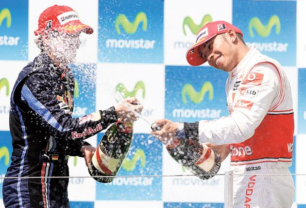Sebastian Vettel celebrates on the podium with Lewis Hamilton