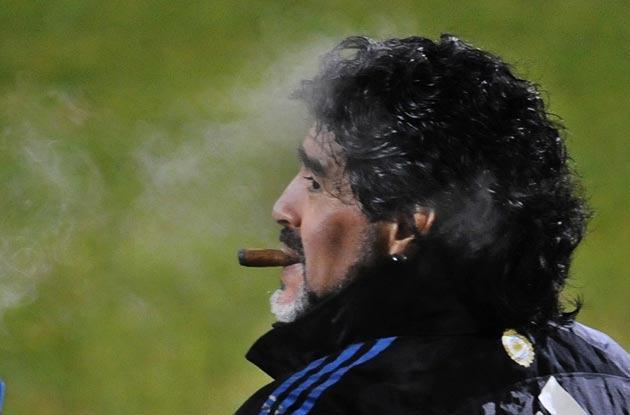 Maradona enjoys a cigar during training
