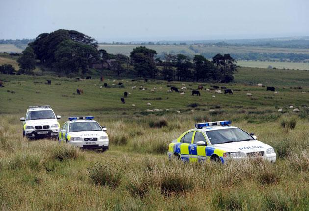 Police vehicles are seen in a field in Rothbury, Northumberland, as they continue the search for Raoul Moat