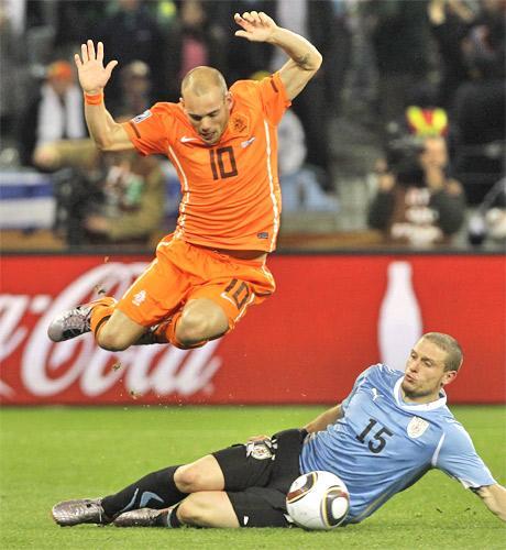 Wesley Sneijder evades the challenge of Uruguay's Diego Perez last night