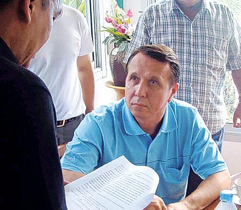 Mikhail Pletnev, in the blue shirt, was served with an arrest warrant at his Pattaya home on Monday. He was later charged with twice raping a boy