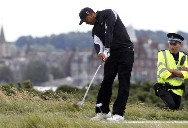 A policeman keeps an eye on Tiger Woods