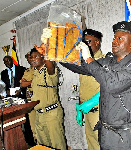 A police officer displays an explosive vest, which was found in a black bag at a club in Kampala's Makindye district