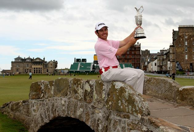 The Open champion Louis Oosthuizen of South Africa shows off the Claret Jug on the Swilken Bridge yesterday