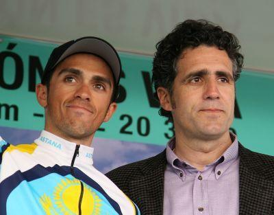Spain's Alberto Contador (L) smiles as he stands on the podium with Miguel Indurain (R).