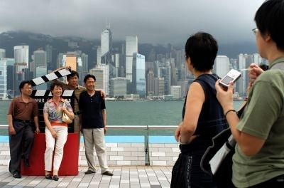 Chinese tourists have their picture taken in front of the Hong Kong skyline.