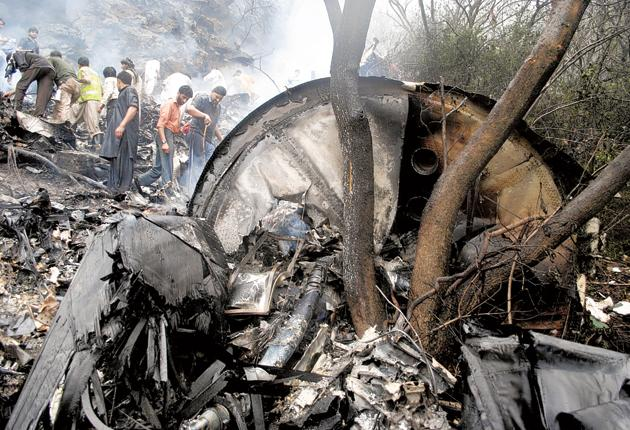 Rescue workers searching for bodies in the wreckage of the plane that crashed near Islamabad killing all on board