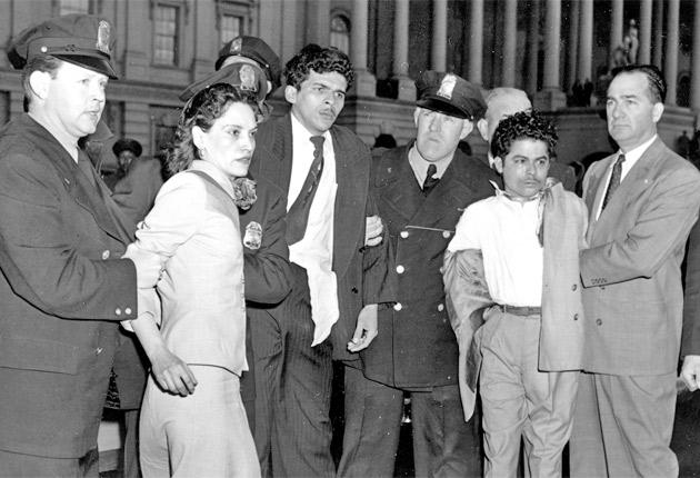 Lebrón is led away by police after her attack on the US House of Representatives in March 1954. Also pictured are her co-conspirators Rafael Cancel Miranda (centre) and Andres Figueroa Cordero (right)