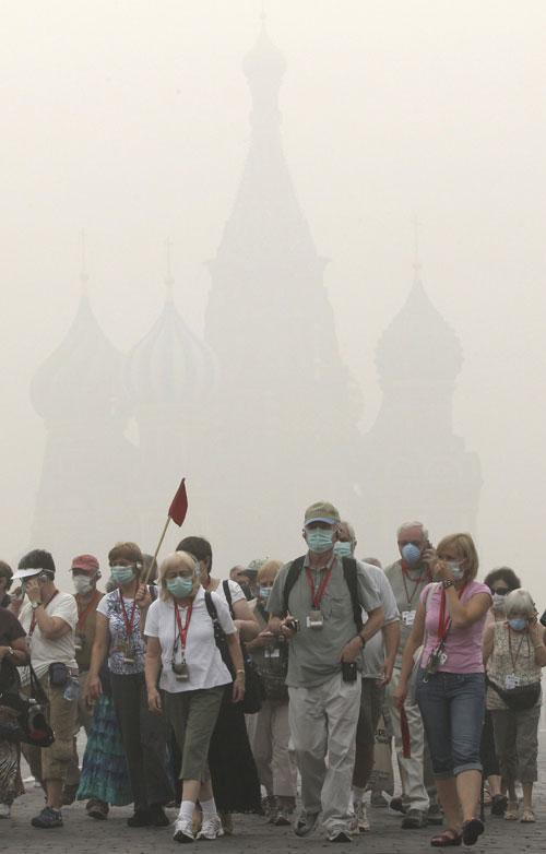 Tourists, wearing masks to protect themselves from heavy smog, walk through Red Square