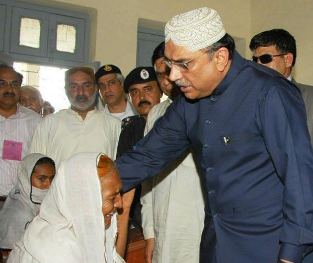 Pakistan's President Asif Ali Zardari visiting a flooded area yesterday