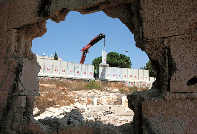 A crane begins dismantling a section of wall separating the Israeli settlement of Gilo from the Palestinian town Beit Jala