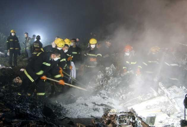 Rescue workers douse the wreckage and search for survivors near Yichun last night