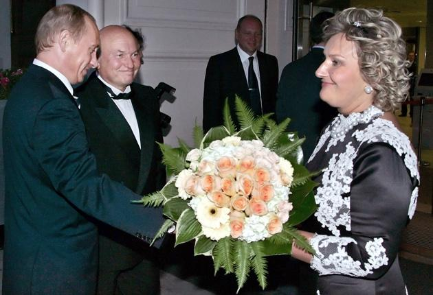 Vladimir Putin presents flowers to Yelena Baturina, wife of Moscow's mayor, Yuri Luzhkov, centre, in 2006