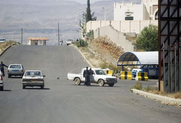 Policemen stop cars near the British embassy in Sanaa after a rocket attack