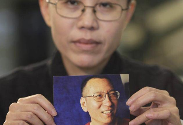 Liu Xia holds a picture of her husband, the Chinese dissident  Liu Xiaobo, in Beijing earlier this month