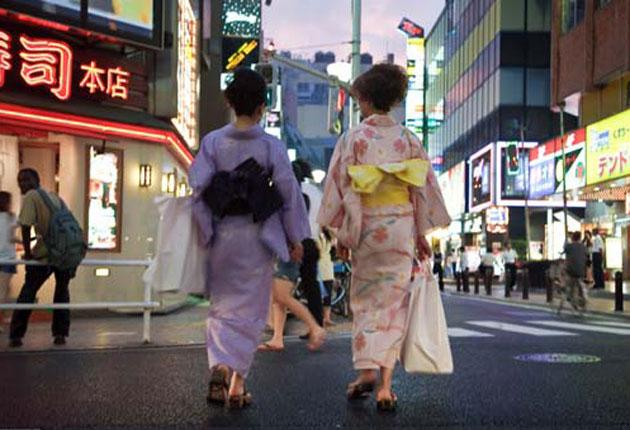Old and new: two traditional geishas make their way through hi-tech Tokyo