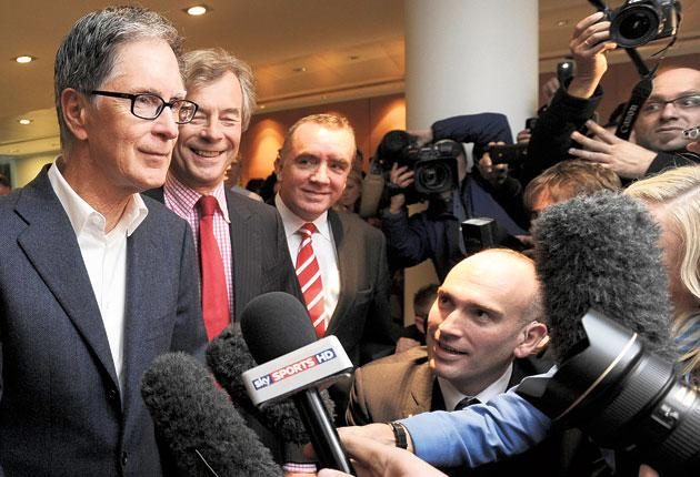 New Liverpool owner John W Henry (left) talks to the media as chairman Martin Broughton (second left) looks on in the City of London yesterday