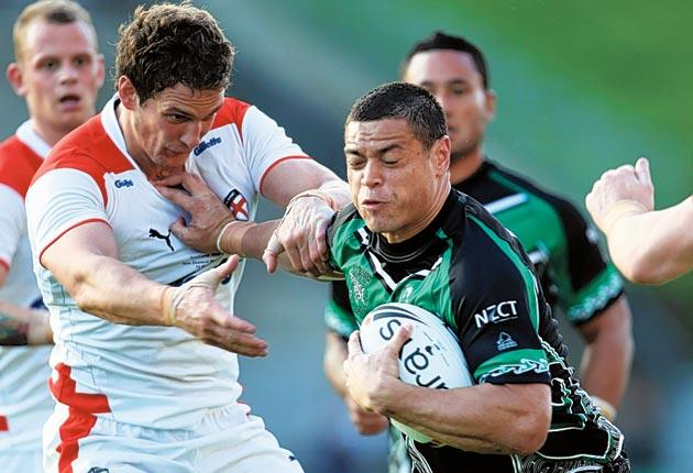 Timana Tahu, of New Zealand Maori, hands off England's Sean O'Loughlin at Mt Smart Stadium in Auckland on Saturday