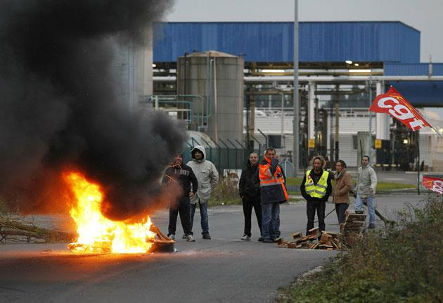 Strikers burn tyres in front of the Total refinery in Grandpuits