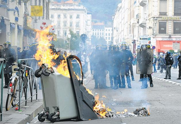 Protesters in Lyon set fire to the city as riot police look on