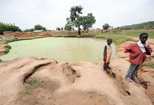 Two boys by a Nigerian pond polluted with lead